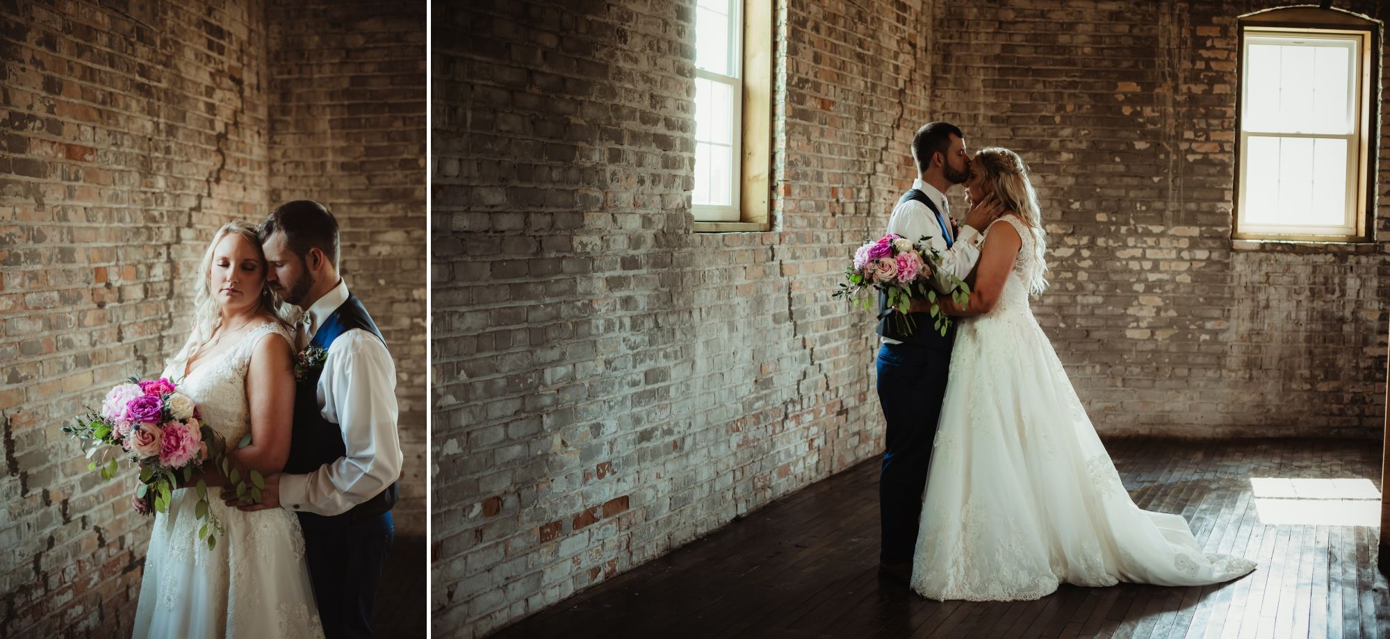 Wedding couple embracing with the groom kissing bride's forehead in an old brick building.