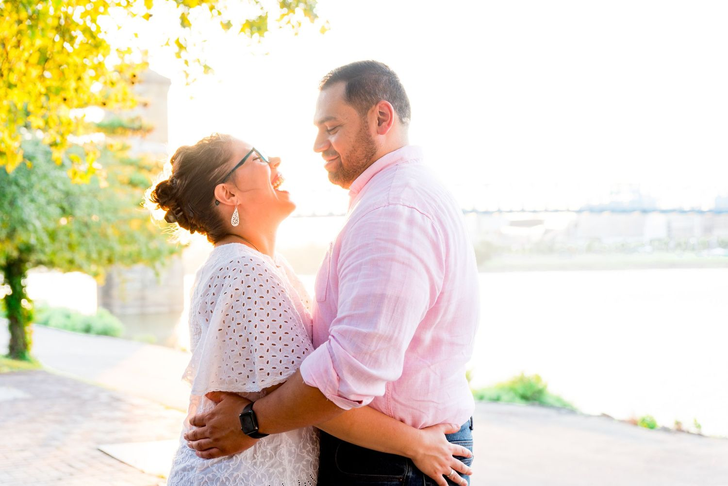 woman in white shirt hugs her fiance in pink shirt and laughs while looking at him under a yellow tree at sunset