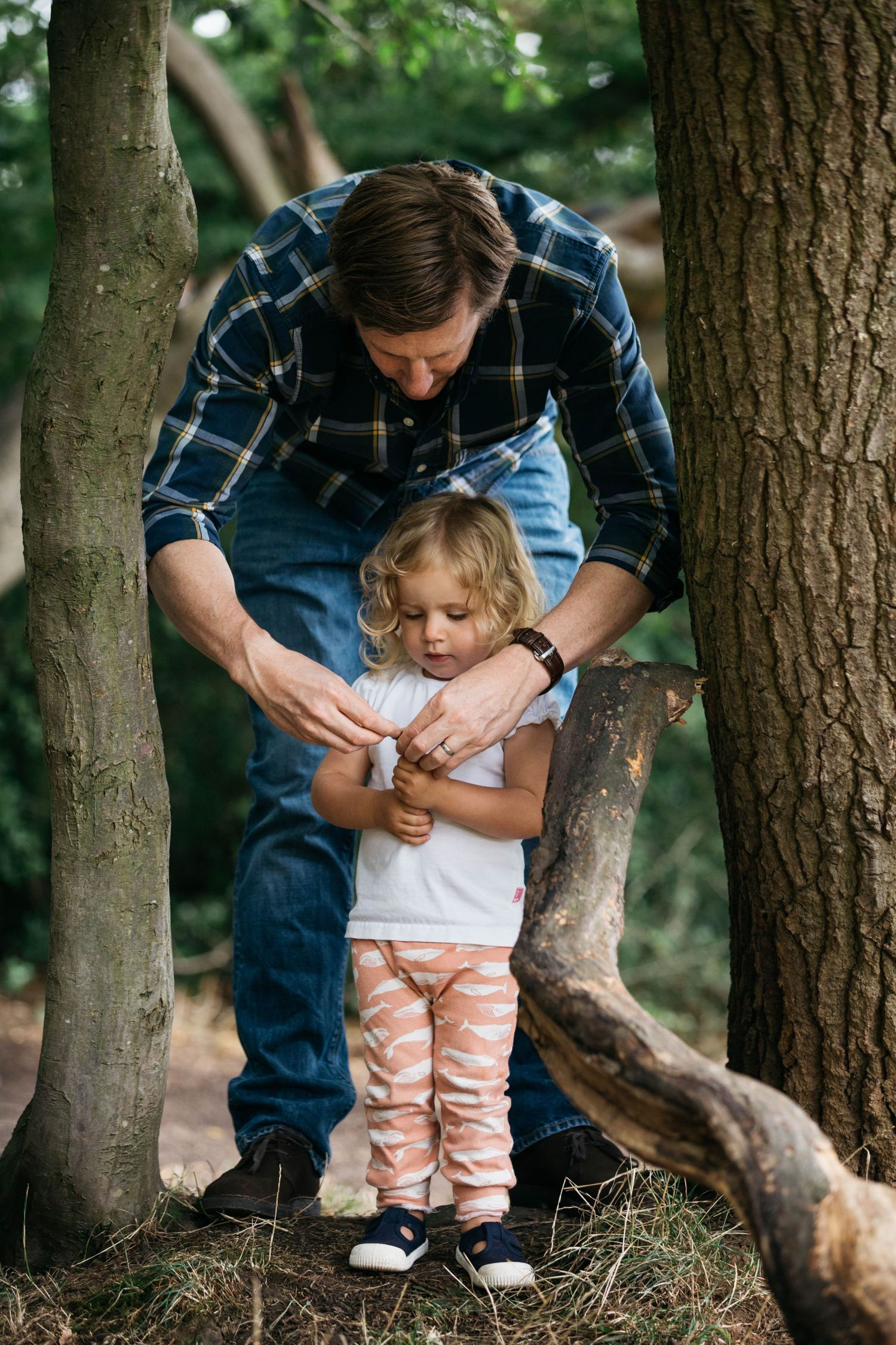 dad and daughter playing with sticks in epping forest east London