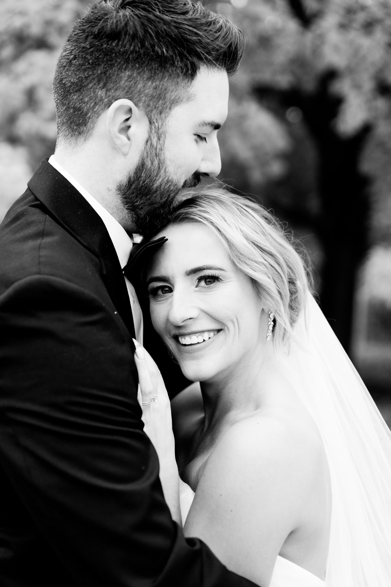 bride lays on grooms chest and smiles at camera while he hugs her