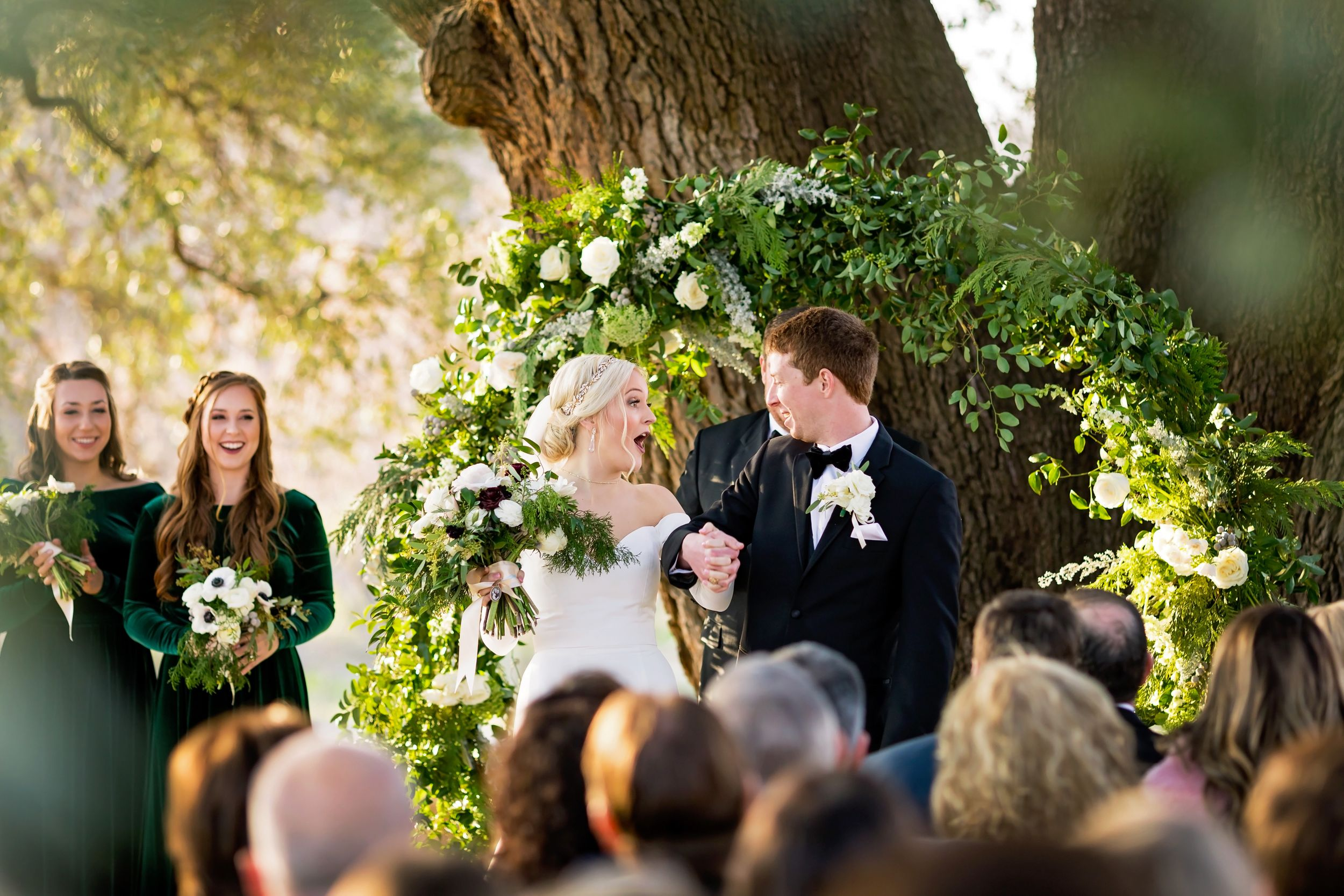 "Bride and groom cheer after they say ""I Do"" during their wedding ceremony, with a floral arch behind them."