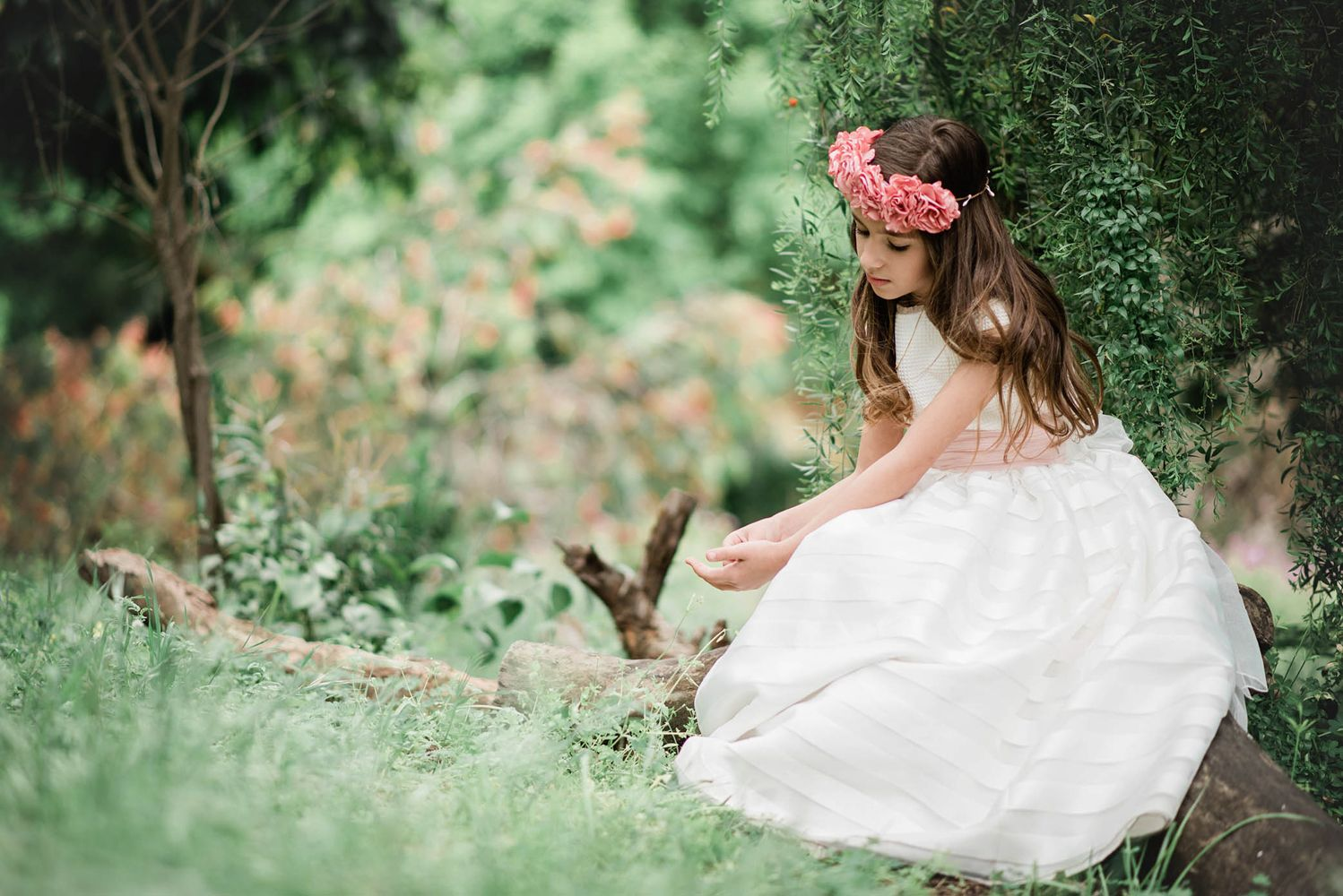 Girl in communion dress sitting in a park with flowers
