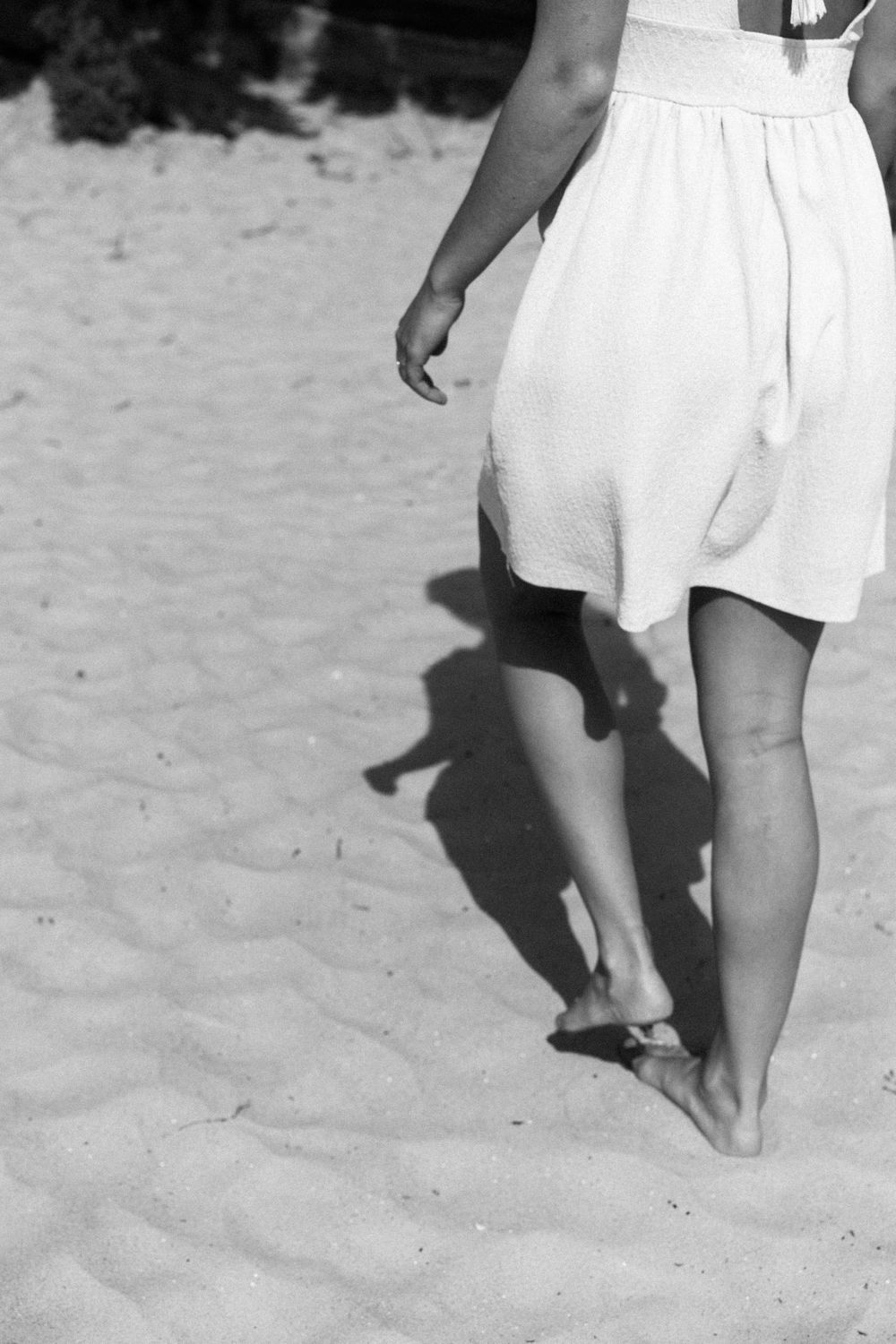 woman in a white dress walking on the beach