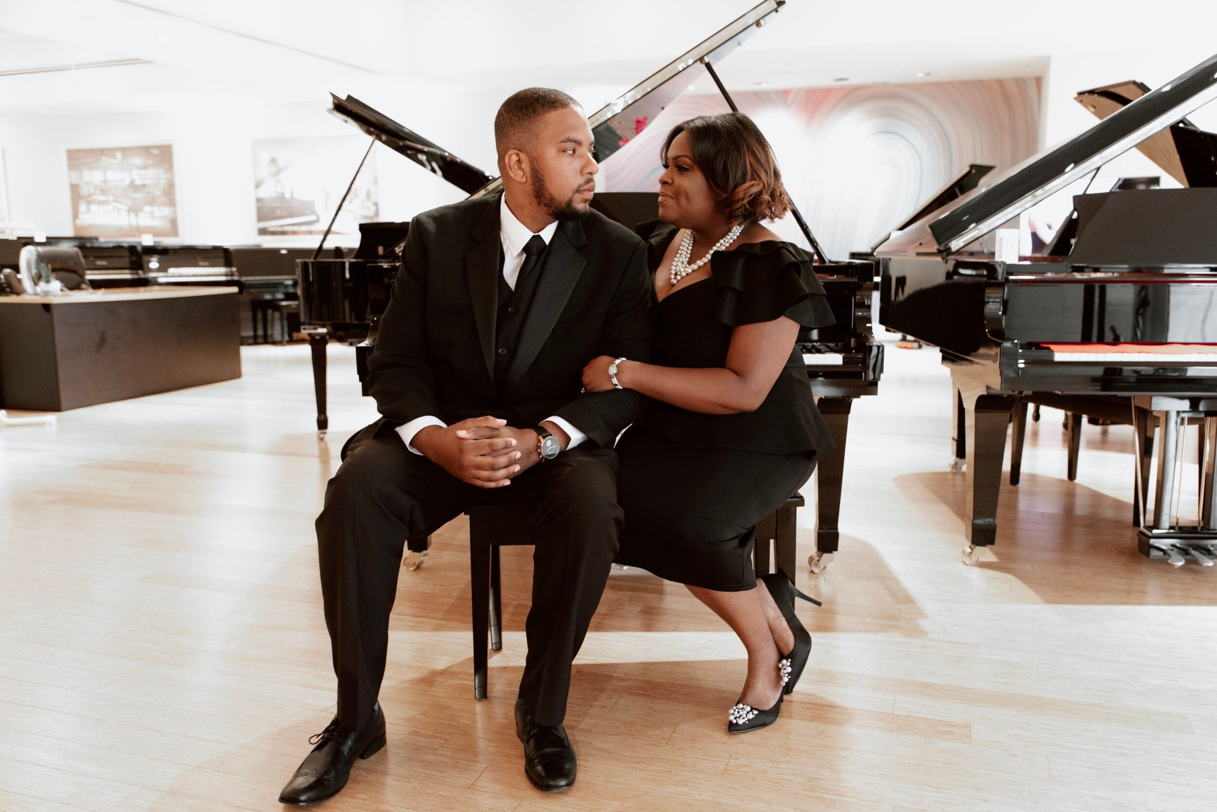 couple wearing all black sitting in piano room