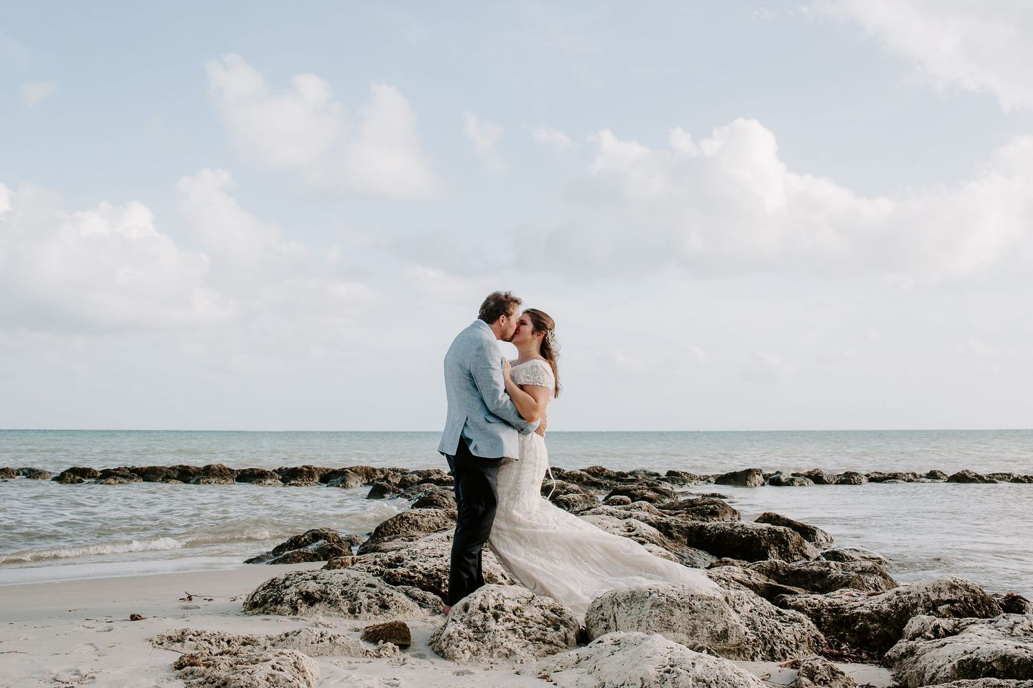 couple embracing and kissing while standing on rocks with the ocean on the background during their Key West elopement