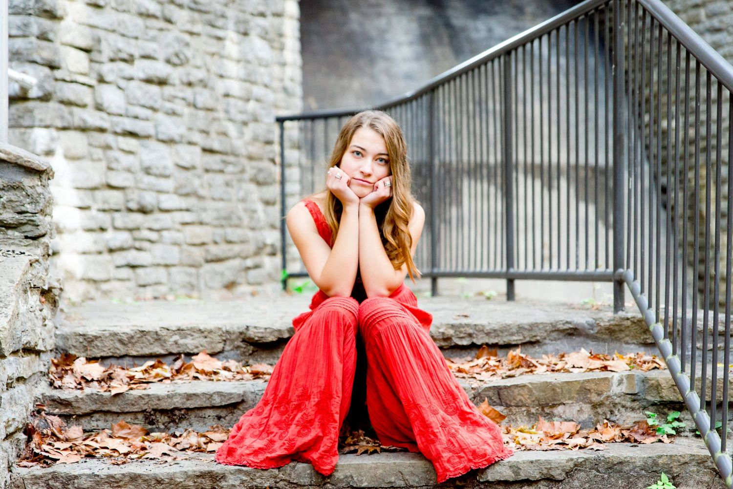 young woman in orange jumpsuit sits on stone stairs with leaves on them in the fall for Chicago senior pictures