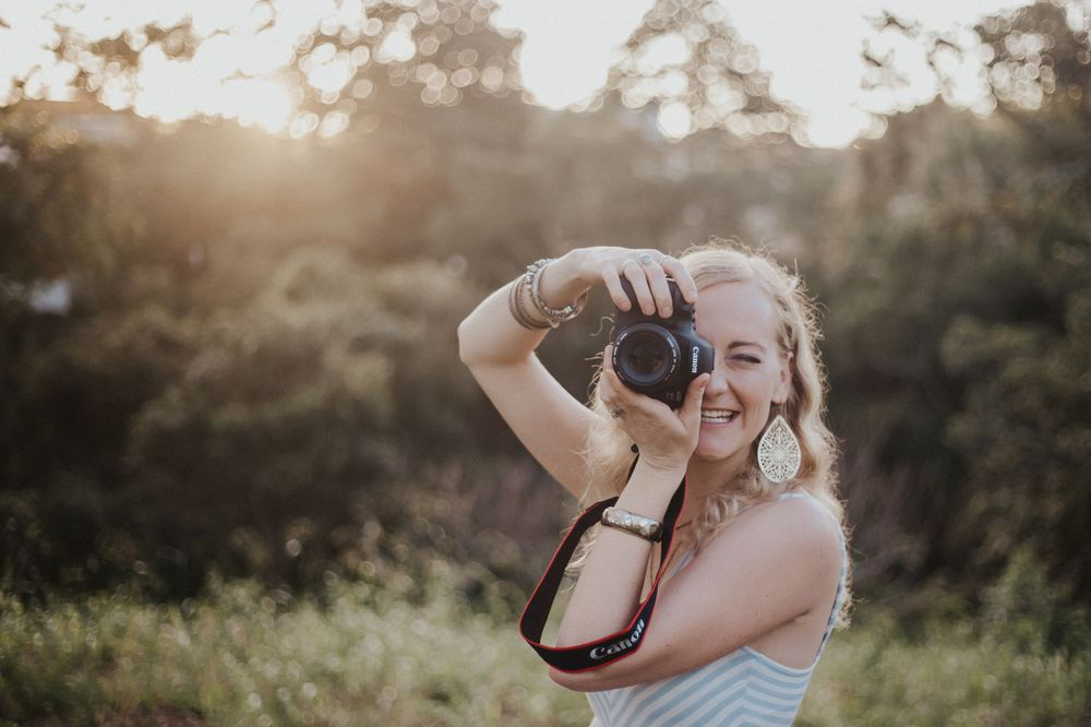 Girl holding camera to take a photo smiles while sun sets behind
