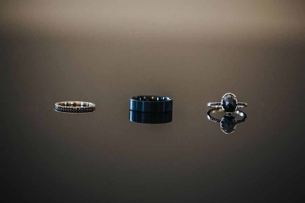 rebecca skidgel photography marina academy san francisco wedding rings on reflective table