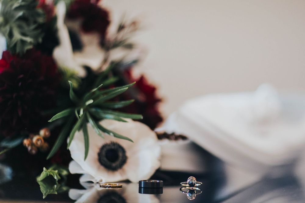 rebecca skidgel photography marina academy san francisco wedding rings on reflective table with bouquet and shoes