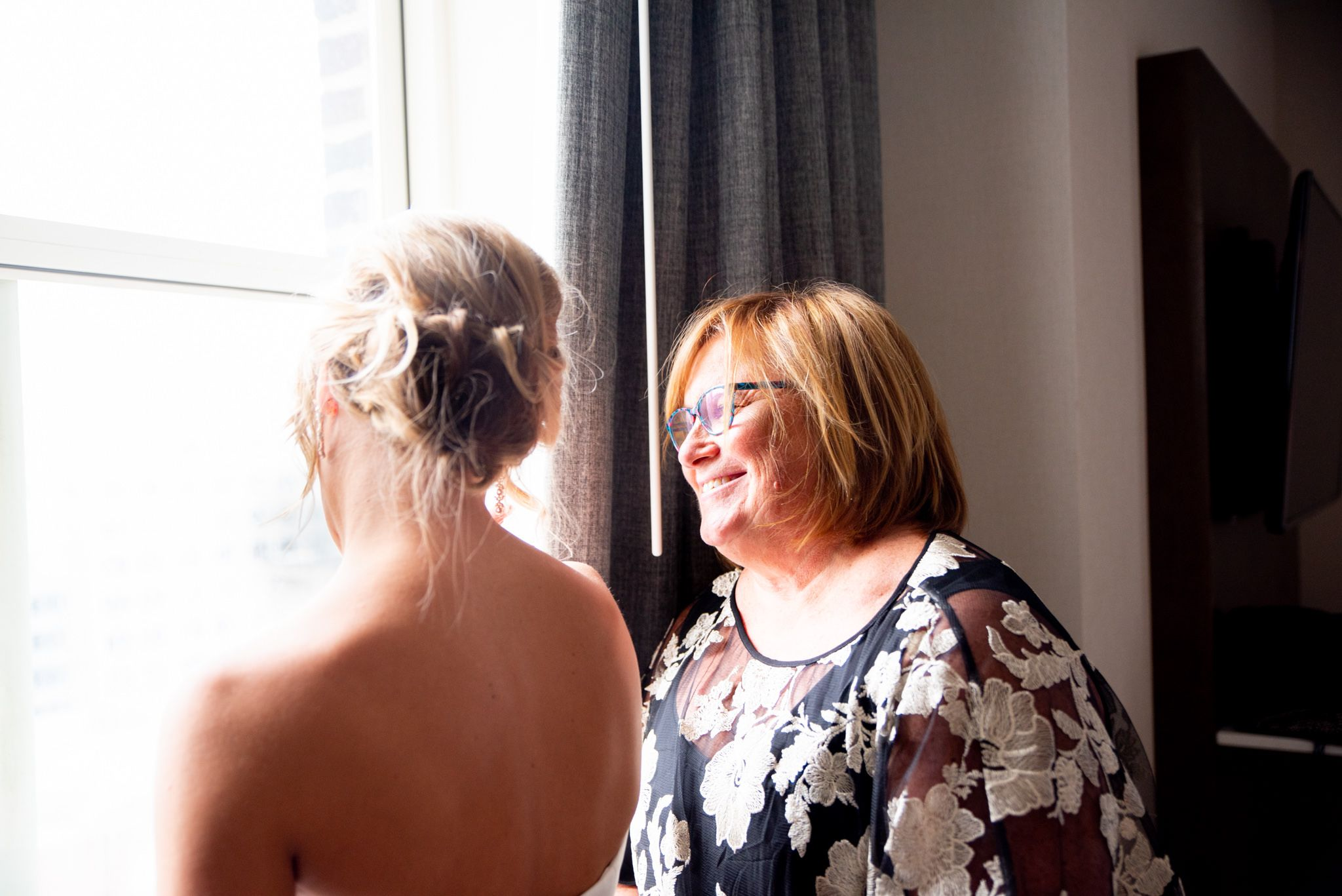 mother of the bride smiling at her daughter while getting ready next to a window