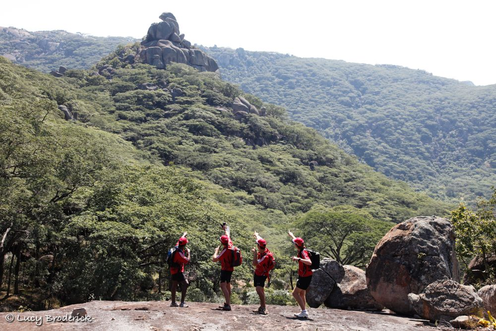 A team of four boys pointing at Dolphin Rock, Matopos, Zimbabwe, Ironwill Charity Eco Challenge.