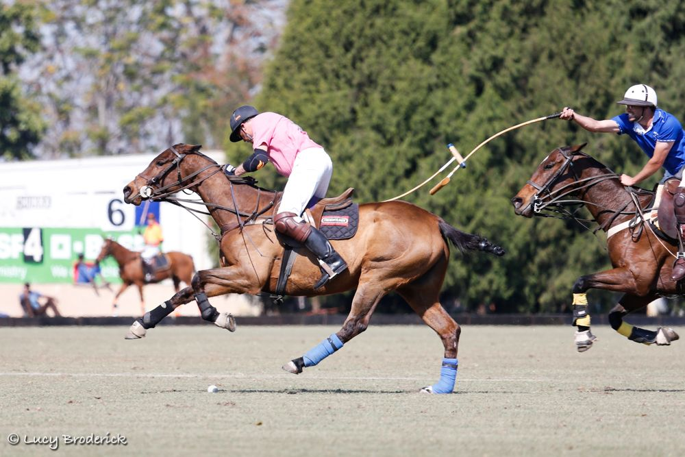 A polo player trying to block another polo player from striking the ball during the Junior Polo Open, Harare, Zimbabwe.