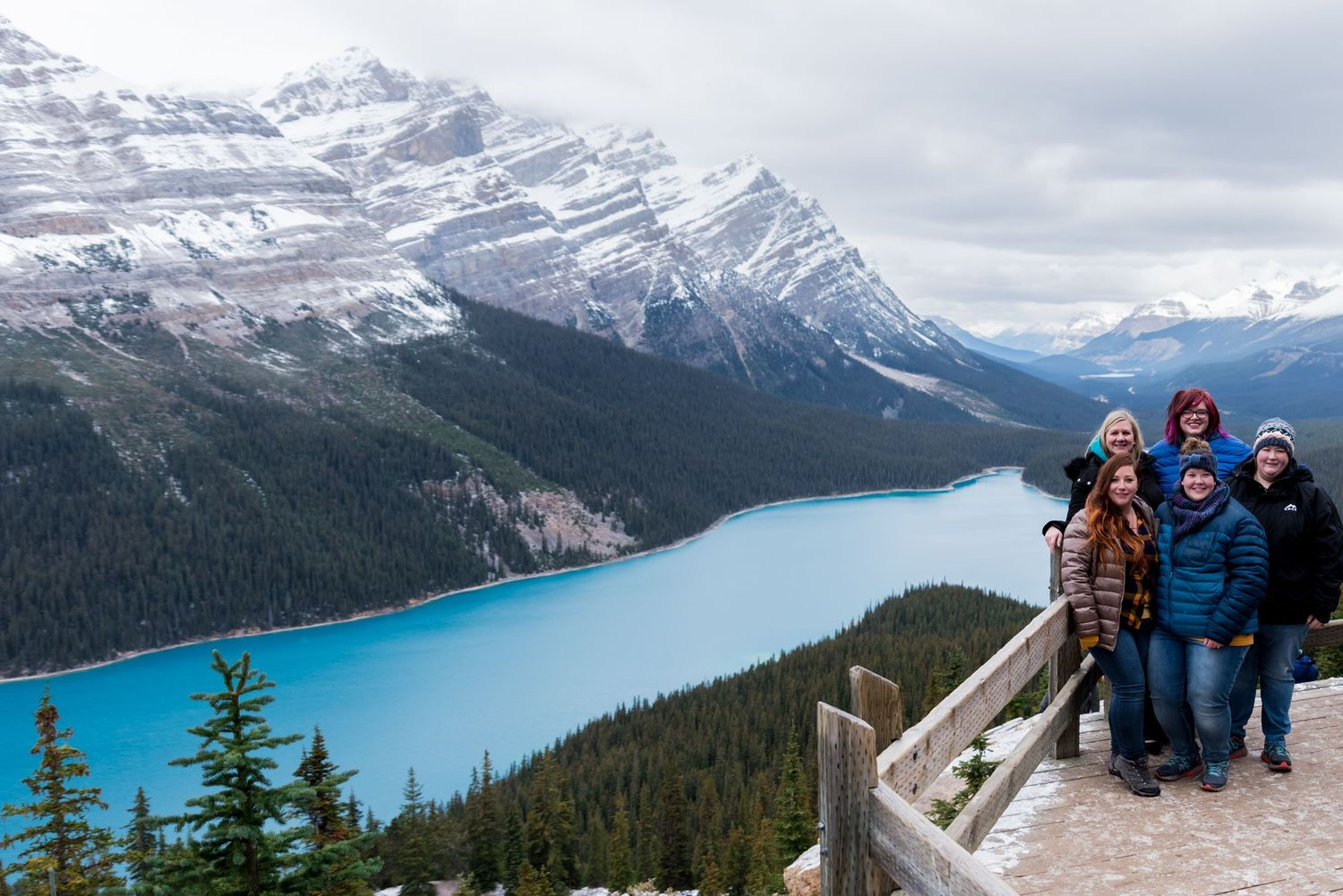 five girls standing on wooden deck in front of Peyto Lake, Canada
