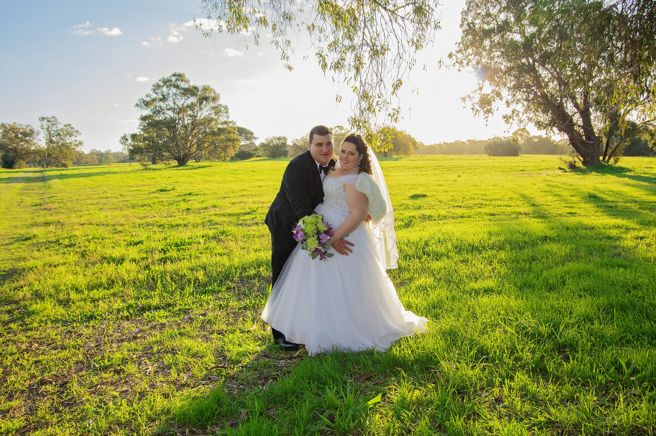 bride and groom posed in grass field
