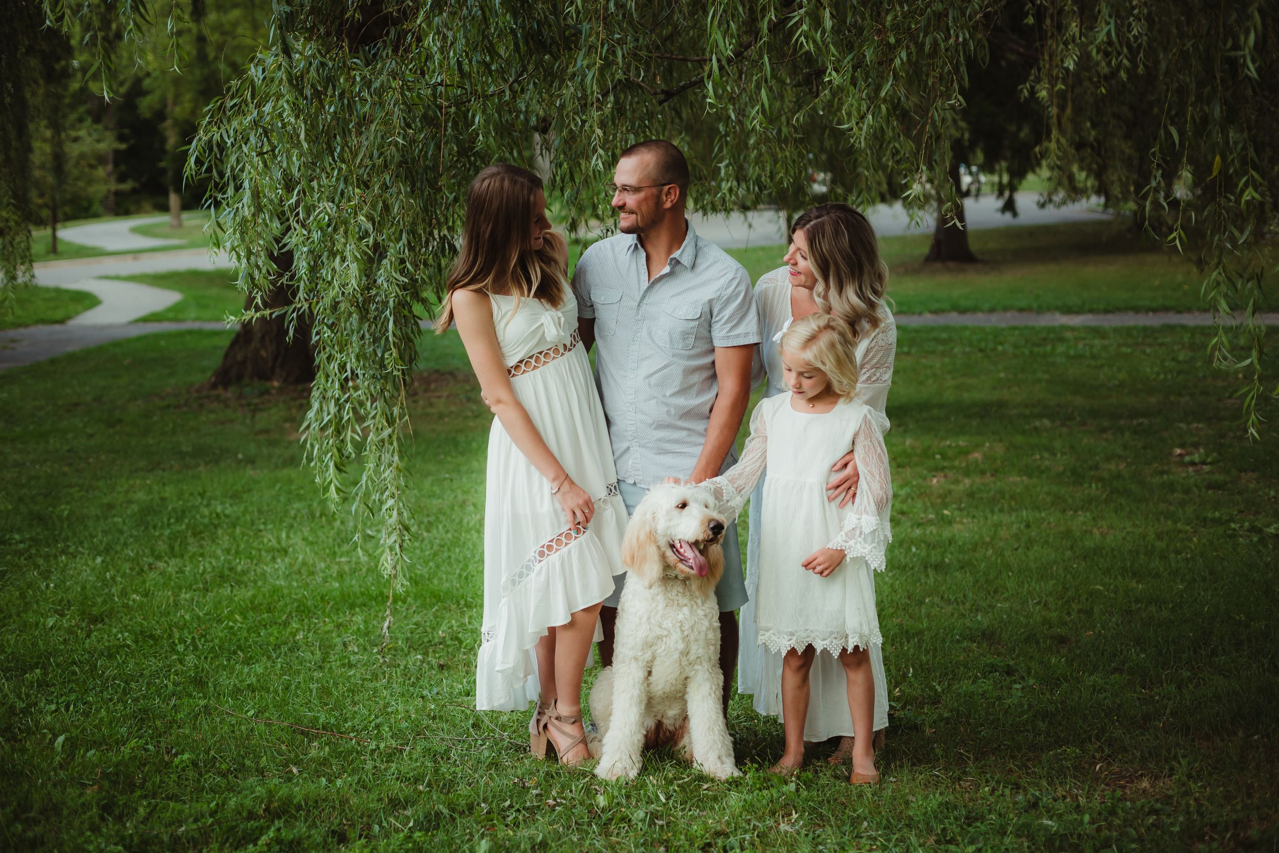 Mom, dad, two daughters, and white dog standing under a willow tree looking at each other.