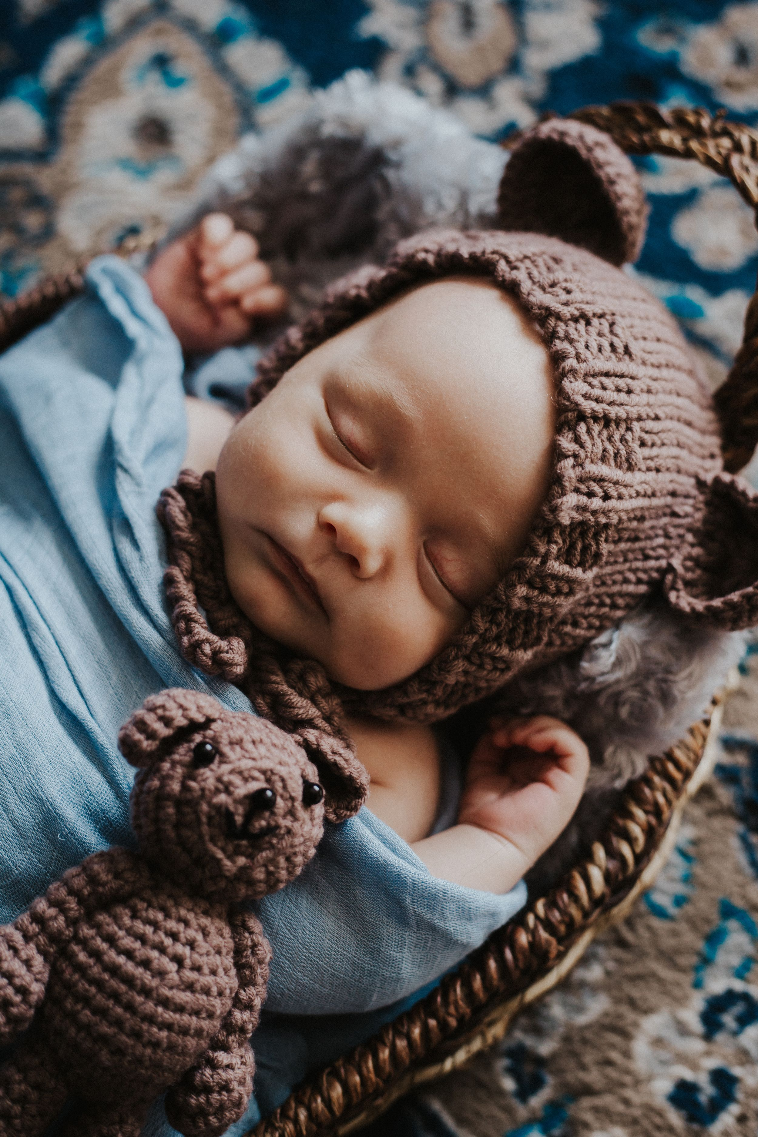 Baby boy in toque with bear ears sleeps during newborn photos