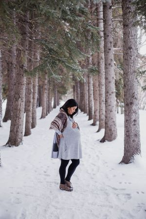 Pregnant woman stands between two lines of trees in Edworthy park Calgary