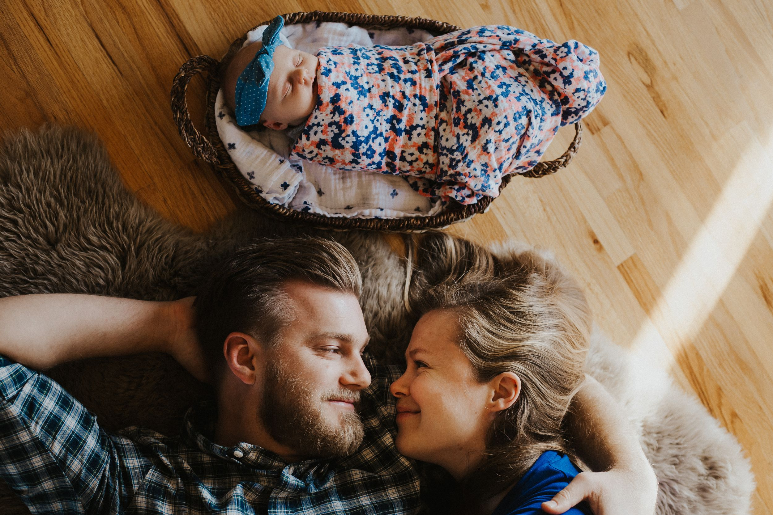 Couple lay on floor looking at each other with newborn baby in basket beside them