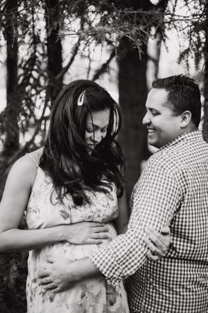 Man and his pregnant wife smile while she touches her belly