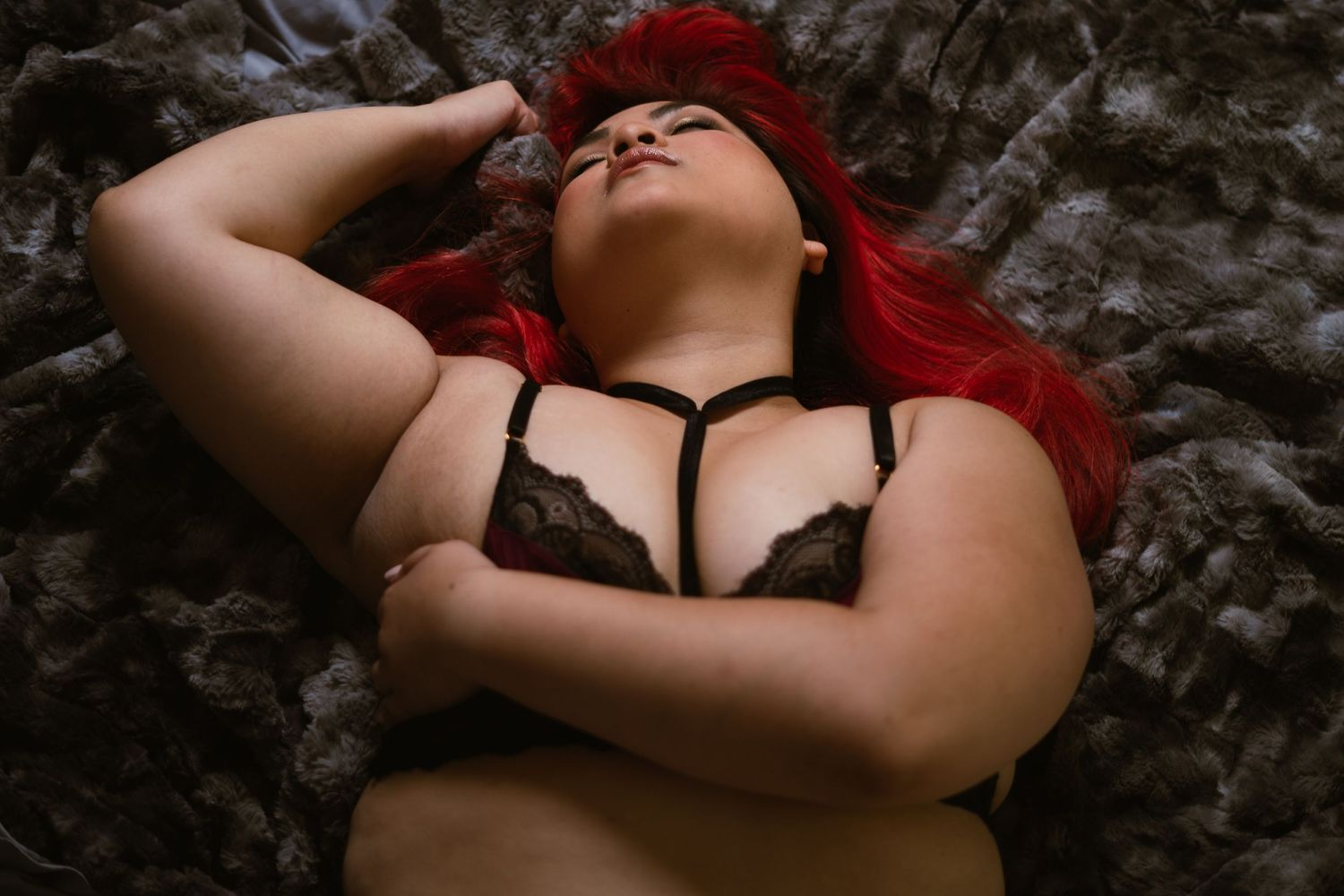 woman in a suggestive boudoir pose laying on her back in a strappy bra, eyes closed and head thrown back