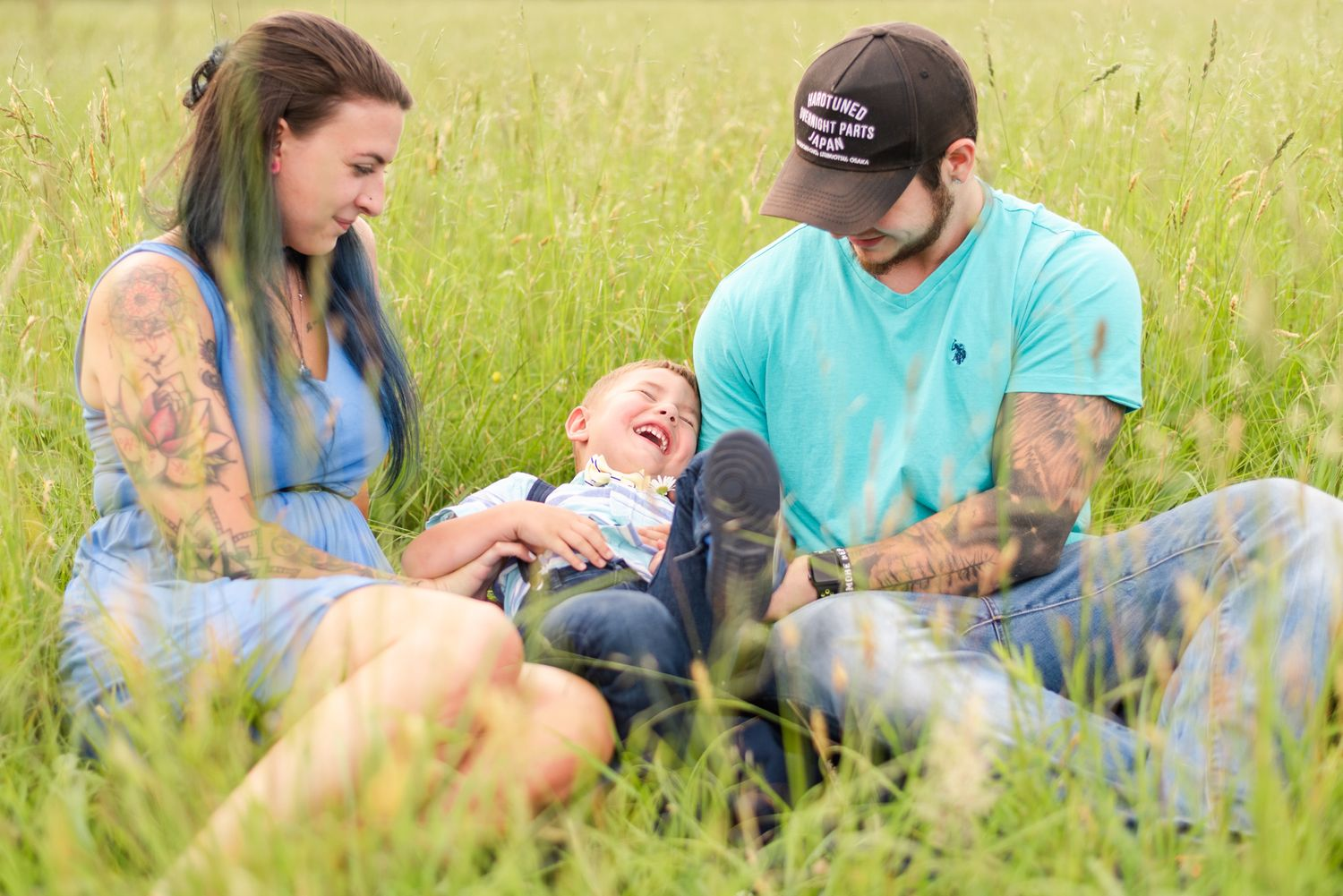 Little boy being tickled in field by mother and father in Clarion Pennsylvania