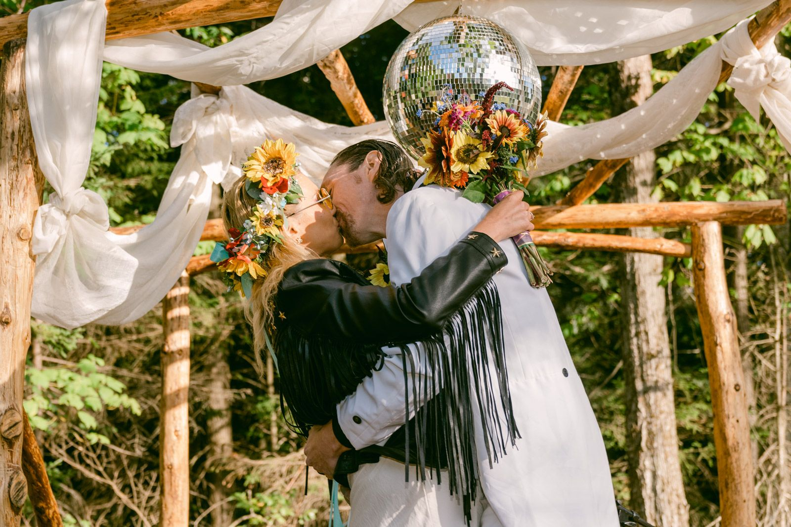Bride and Groom kissing under a disco ball outdoors