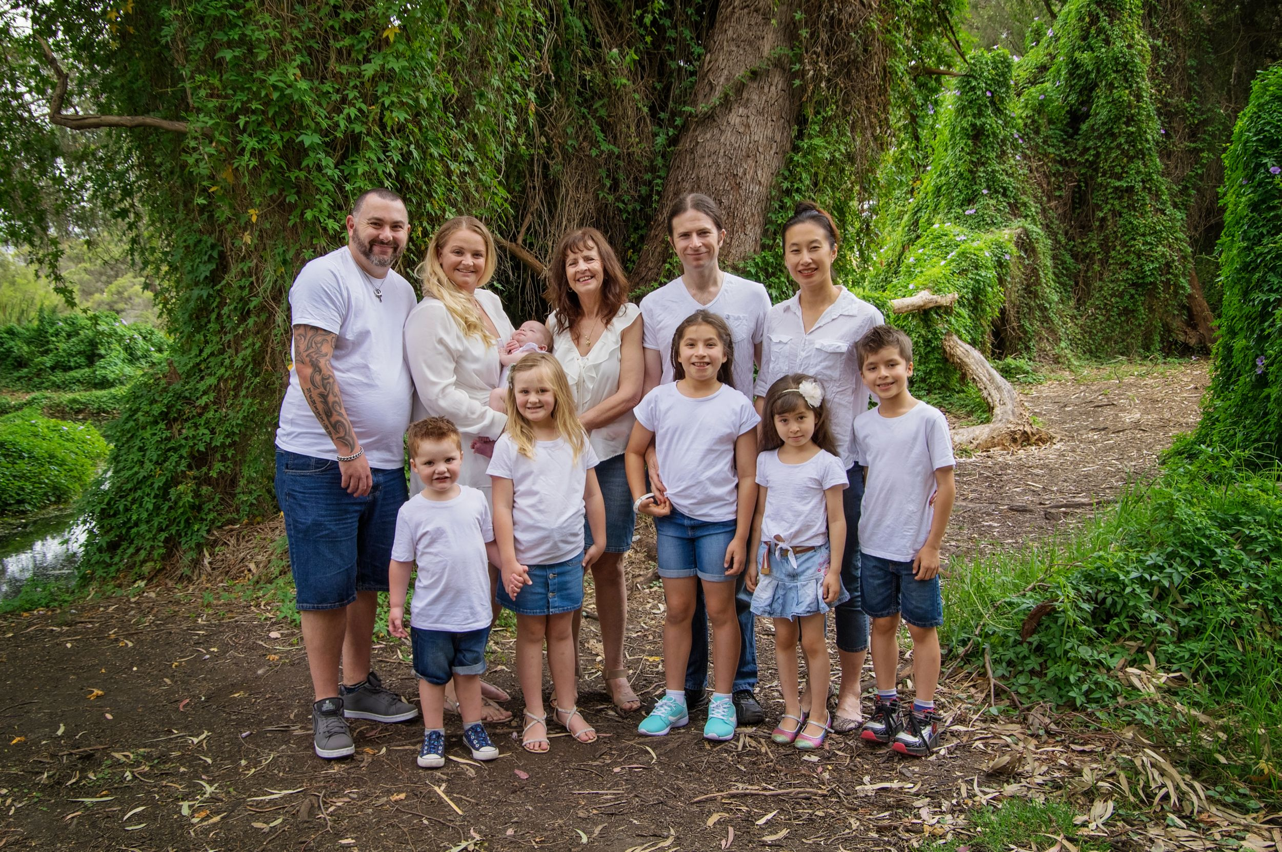 Family portrait outside witih adults and children dressed in white and blue smiling at camera
