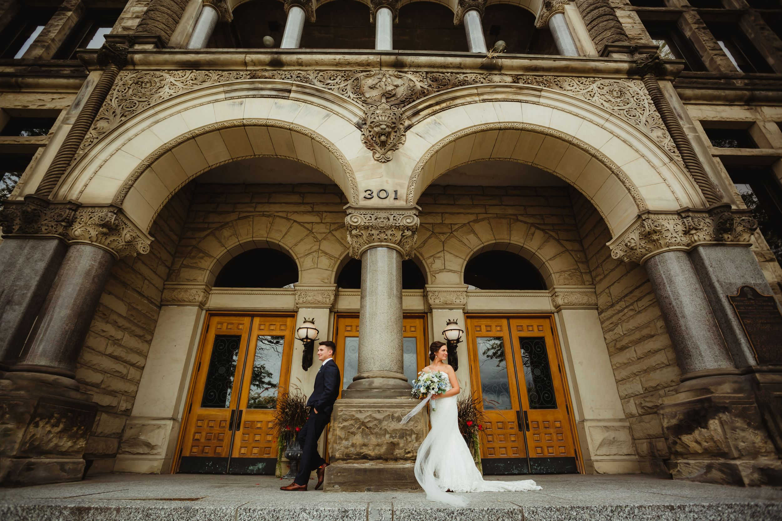 Bride and groom standing on either side of a pillar at the courthouse in Bay City.