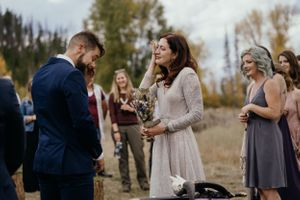 bride-and-groom-saying-vows-while-crying-during-ceremony-elopement-at-double-a-barn-grand-lake-colorado-raelyn-ramey
