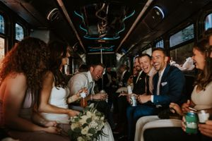 groom-laughing-on-party-bus-with-wedding-party-desmoines-iowa-raelyn-ramey-photography