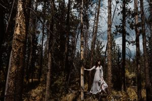 bride-standing-in-woods-double-a-barn-grand-lake-colorado-raelyn-ramey-photography