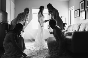 bride-getting-ready-bridesmaids-holding-veil-desmoines-iowa-raelyn-ramey-photography