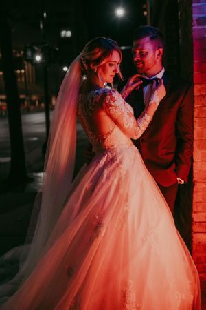 bride-fixing-grooms-tie-in-front-on-neon-lights-downtown-desmoines-iowa-raelyn-ramey-photography
