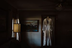 detail-shot-of-a-dame-and-maiden-wedding-dress-hanging-up-desmoines-iowa-raelyn-ramey-photography
