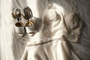 bride-details-dress-shoes-sitting-on-bed-savory-hotel-raelyn-ramey-photography