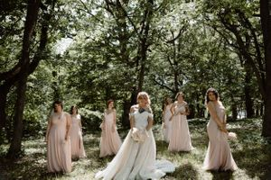 bride-and-bridesmaids-posing-in-woods-summerset-winery-indianola-iowa-raelyn-ramey-photography