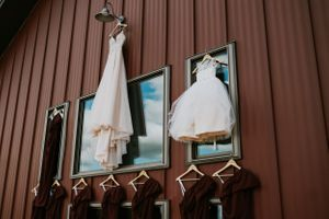 bride-dress-and-bridesmaids-dresses-hanging-on-barn-carper-winery-norwalk-iowa-raelyn-ramey-photography