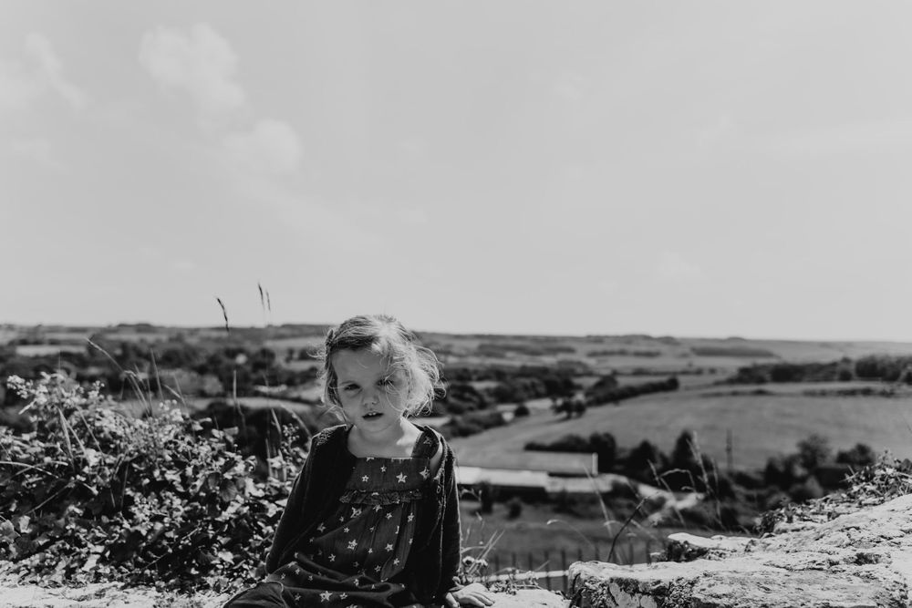 Two year old girl stares into the lens against a countryside landscape.