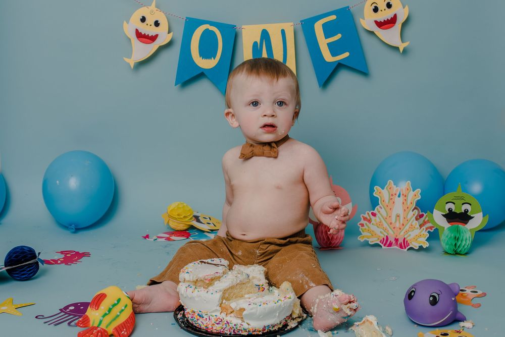 one year old boy cake smash session with balloons and shark doo doo
