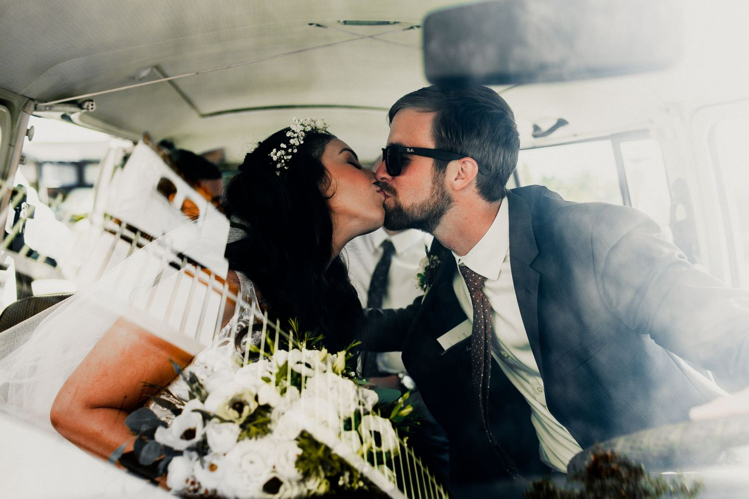 bride and groom first kiss inside volkswagon van