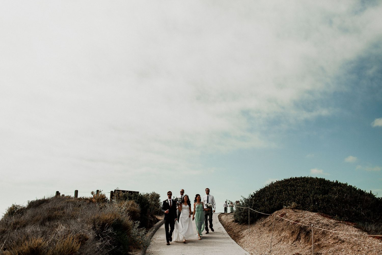 bridal party walking down to crystal cove beach