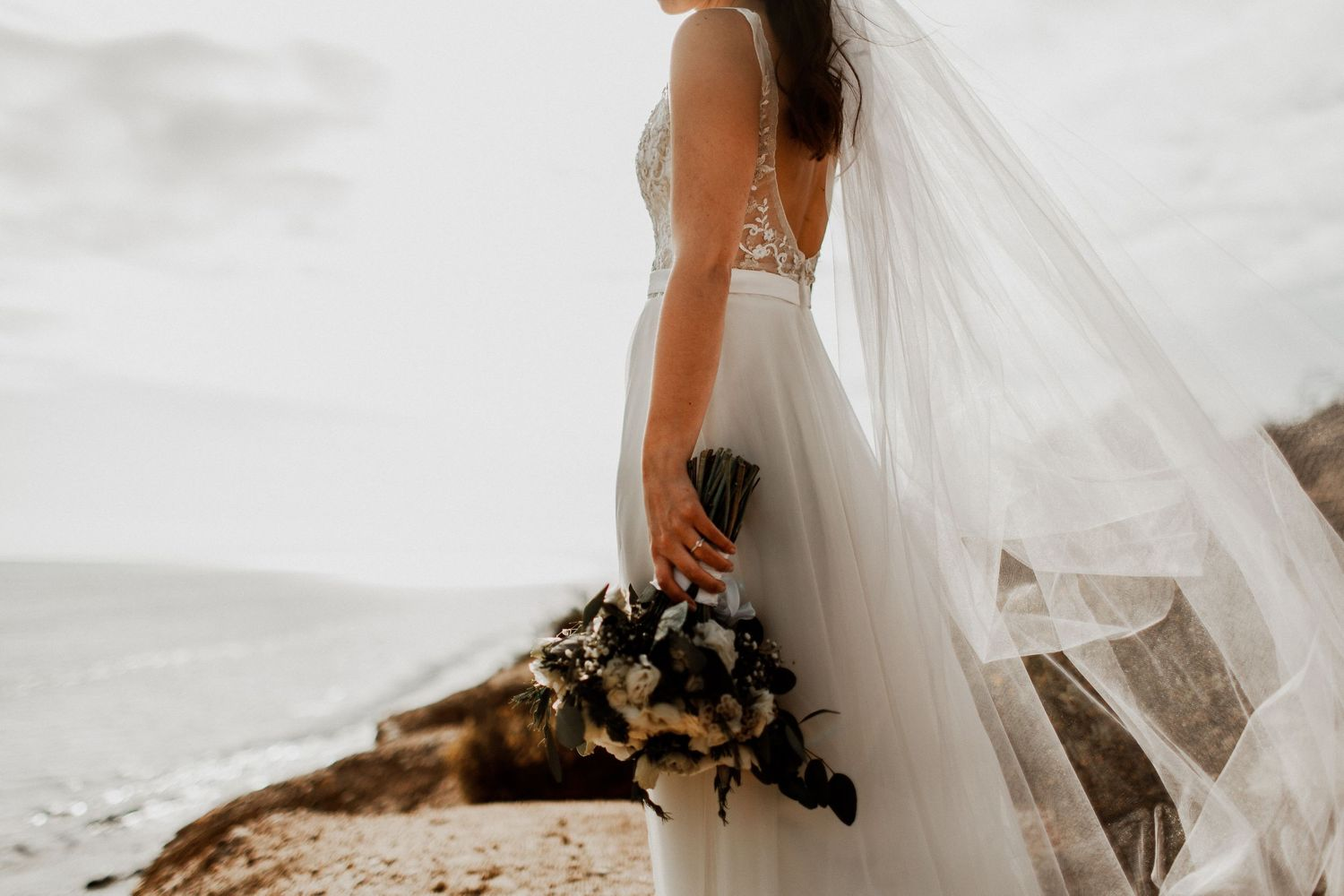 bride solo picture with bouquet flowing with the wind