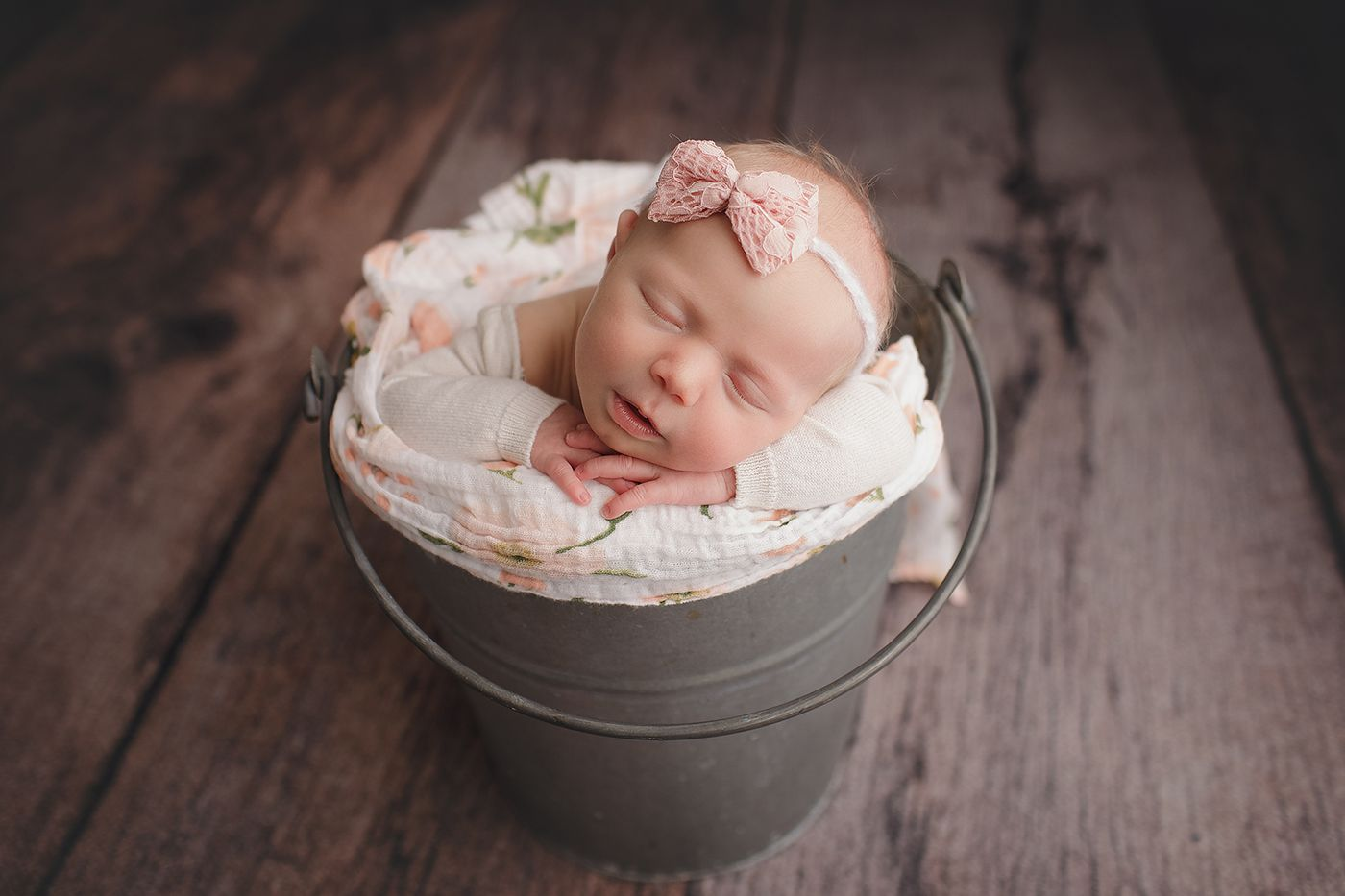 Baby girl in a bucket in a Perth newborn photography studio
