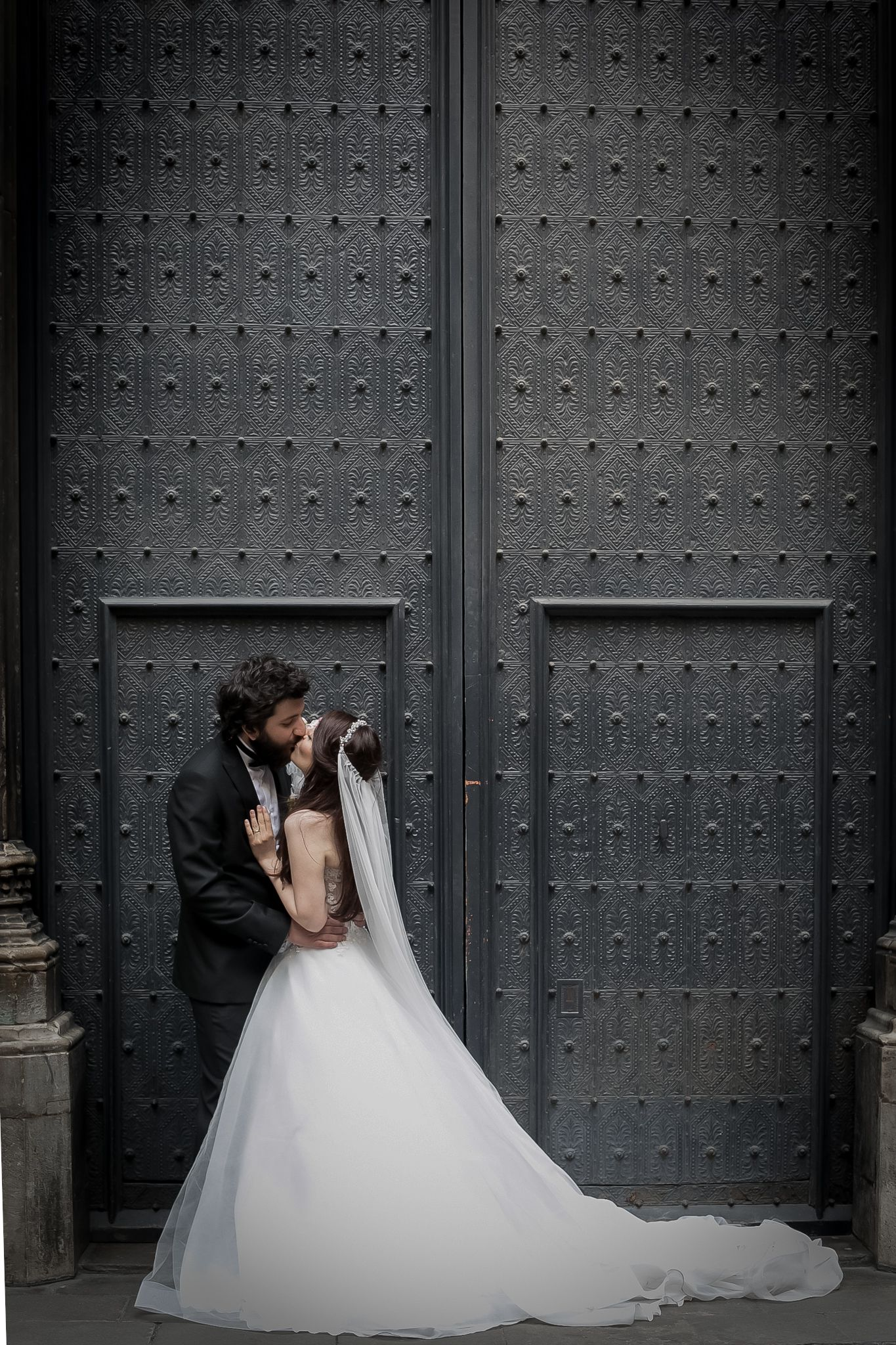 Bride and Groom kiss in front of tall doors