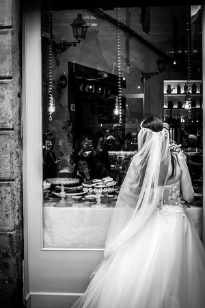 Bride looking at a cake through the window in Barcelona