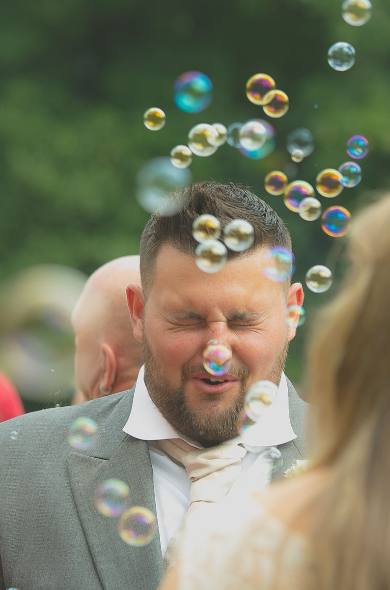 Bubbles blow in front of the best man's face during a wedding reception