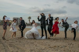 Wedding party jump in the air on the beach in Barcelona