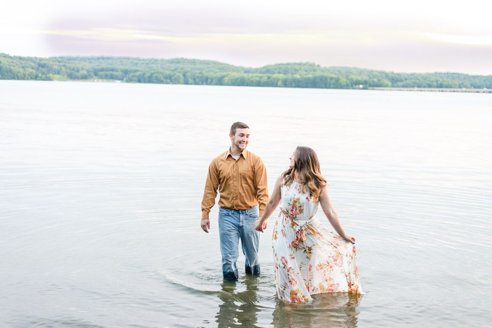 Couple laughing holding hands for engagement in Lake Arthur at Moraine State Park in Pennsylvania