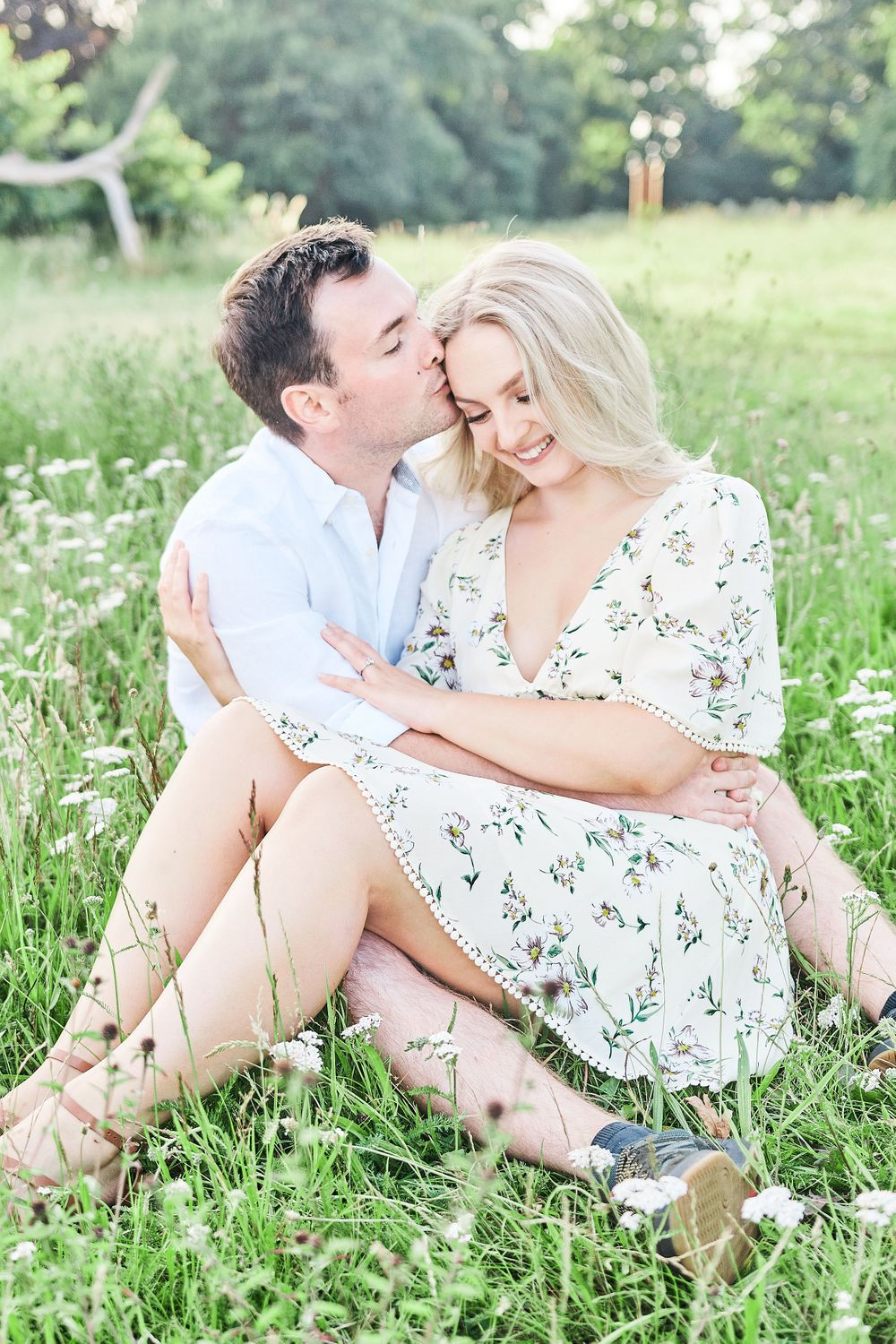 beautiful couple sit amongst wildflower meadow for engagement shoot at Catton Park, Norwich