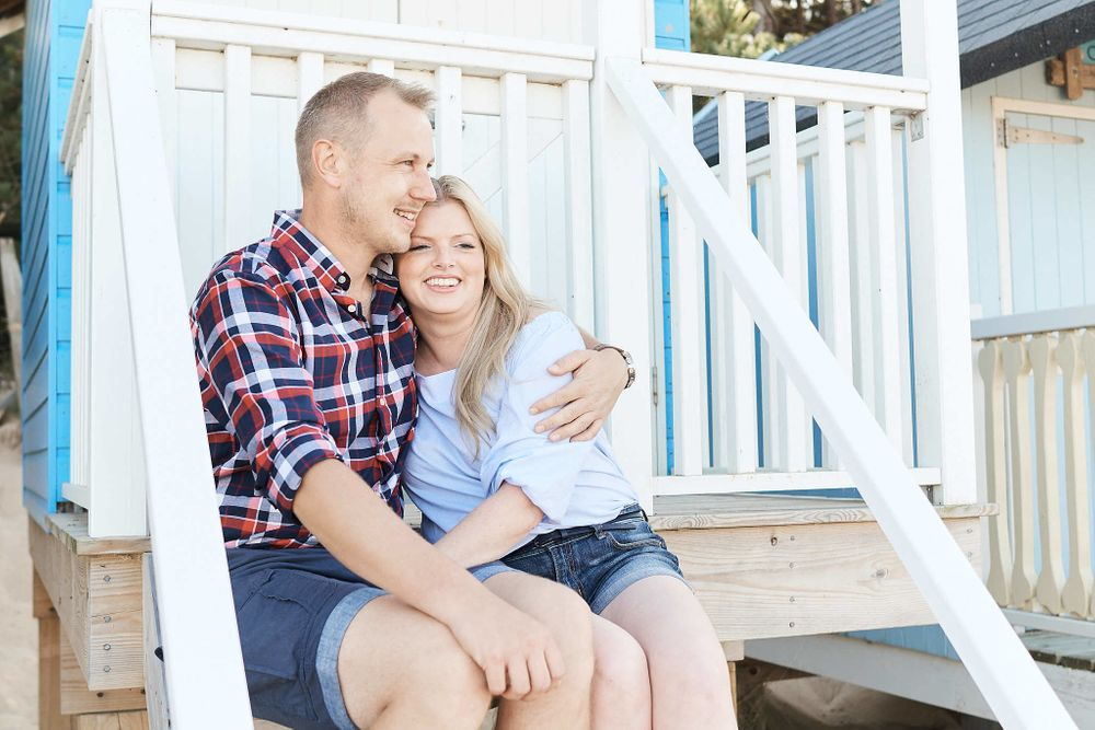 newly engaged couple share a cuddle sitting on the steps of a Norfolk beach hut by wedding photographer Faye Amare